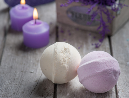 bath: SPA still life,bath bombs closeup with violet flowers on wooden background.