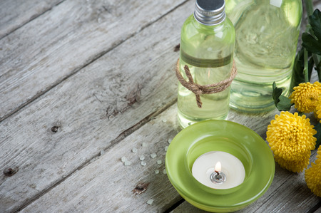 lit candle: SPA still life, green lit candle, bath products, wooden background