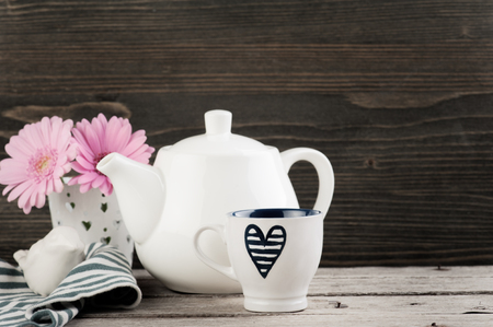 Navy blue heart cup, white teapot and pink daisies on dark wooden background. Toned image Stock Photo