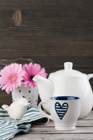 navy blue background: Navy blue heart cup, white teapot and pink daisies on dark wooden background. Toned image