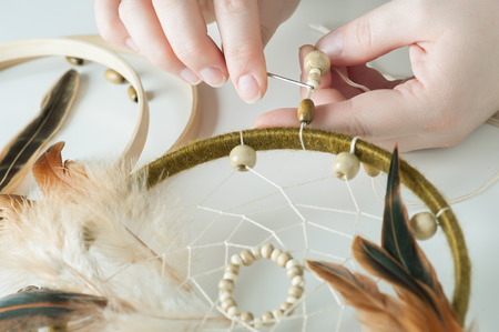 Close-up of female hands having dream catcher assembled. Handmade workshop composition of feathers, beads, threads, tools for DIY