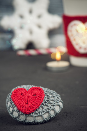 warmer: Christmas decoration crochet stone with red heart. Mug and warmer over rustic wooden background Stock Photo