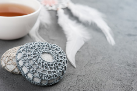 crocheted: Cup of tea and crocheted pebbles closeup on concrete background. Shallow focus, toned image Stock Photo