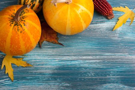 Autumn pumpkins on shabby blue background. Fall harvest flat lay
