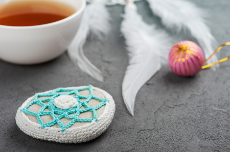 crocheted: Cup of tea and crocheted pebble closeup on concrete background. Shallow focus