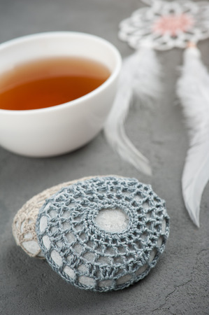 Cup of tea and crocheted pebbles closeup on concrete background. Shallow focus, toned image Stock Photo