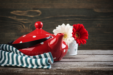 Polka dot red tea pot and flowers on the weathered wood table. Tea time concept