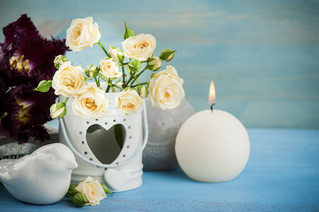 Vintage still life. Bouquet of white roses, purple tulips, blue wooden background and a burning candle, vintage decor