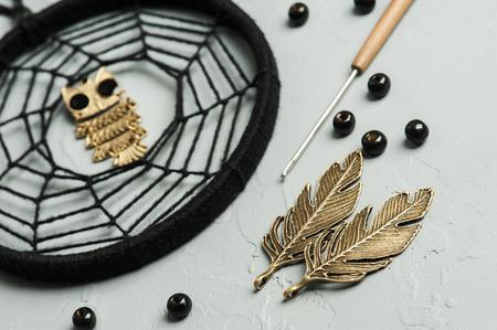 hallowen: Black dream catcher on concrete background with metal owls and beads. Hallowen decor still life