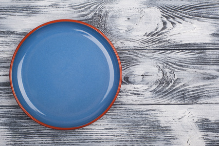 Empty blue plate on wooden background. View from above with copy space Stock Photo