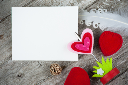 Photo holder with blank card and red heart box on concrete background. Place for photograph or text, flat lay, view from above