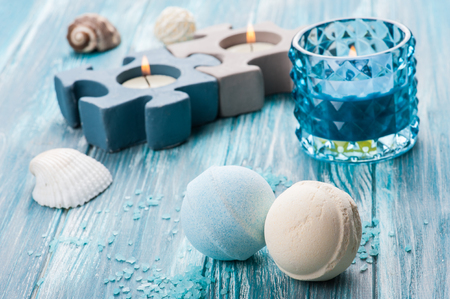 SPA still life, closeup of blue lit candle and bath bombs on wooden background