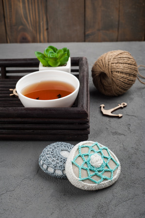 crocheted: Cup of black tea and crocheted pebbles closeup on concrete background. Zen and mindfulness concept