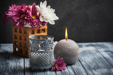Beautiful spa composition with lit candles and chrysanthemum on wooden background. Space for text