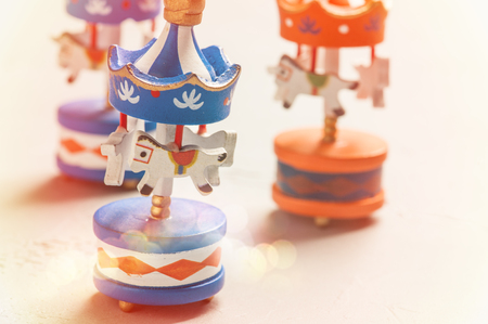 Colorful carousels wooden toys on concrete backgound. Place for text, baby shower or celebration concept. Toned image