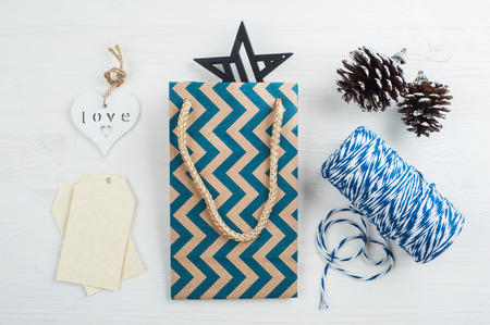 pinecones: Christmas present wrapping backgrownd. Flat lay with shevron bag, wooden heart, pinecones.  Modern lifestyle composition in scandinavian style