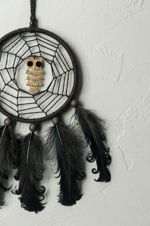 hallowen: Black dream catcher with metal owls and feathers. Hallowen decor still life Stock Photo