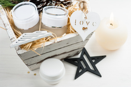 Beauty products and cosmetics with Christmas decoration and lit candle composition in shabby white wooden basket