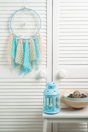 crocheted: Blue beige dream catcher with crocheted doilies in the interior with decor and lit candle Stock Photo