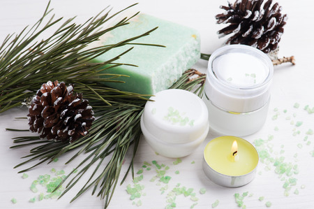 Beauty products and handmade soap with Christmas decoration and lit candle composition on shabby white wooden table Banco de Imagens
