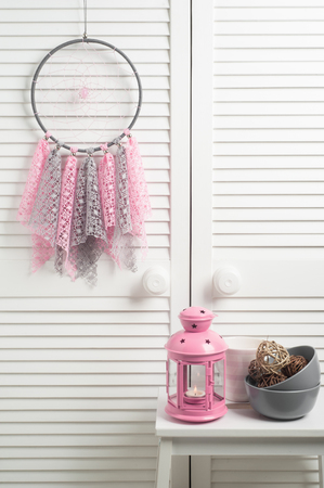 crocheted: Pink beige dream catcher with crocheted doilies in the interior with decor and lit candle