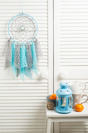 crocheted: Blue grey dream catcher with crocheted doilies in the interior with decor and lit candle Stock Photo