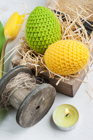 Green yellow crocheted easter eggs in a shabby wooden box with lit candles and tulip on a white table background