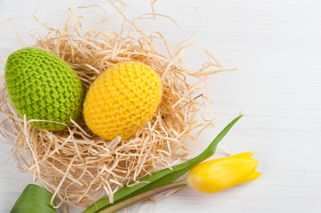 Green yellow crocheted easter eggs with tulip on a white table background