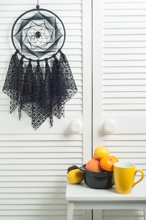 Black dream catcher with crocheted doilies in the interior with lemon, yellow mug and tangerines Stock Photo