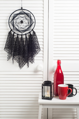 crocheted: Black dream catcher with crocheted doilies in the interior with red bottle, mug and lit candle