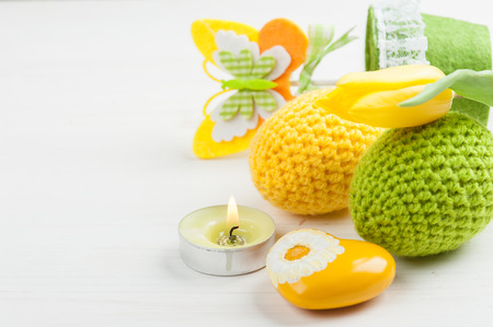 Green yellow crocheted easter eggs and yellow heart with lit candles and tulip on a white table background