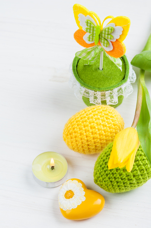 crocheted: Green yellow crocheted easter eggs and yellow heart with lit candles and tulip on a white table background
