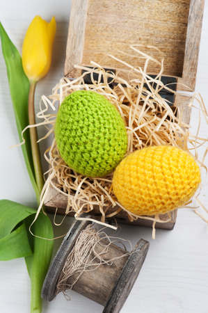 Green yellow crocheted easter eggs in a shabby wooden box with tulip on a white table background