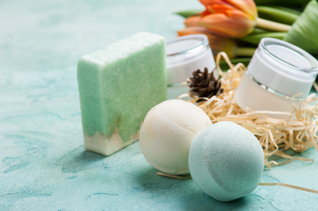 Green bath bomb and soap with SPA products on blue concrete background. Bathroom composition
