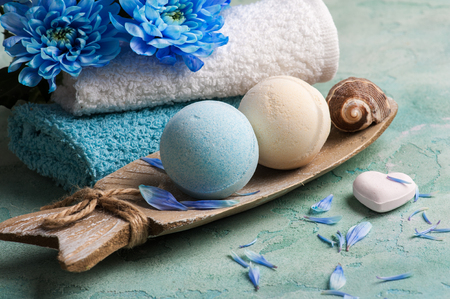 SPA treatment. Blue flowers and bath bombs on concrete background.