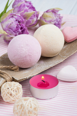 bougie coeur: Vanilla and strawberry bath bombs, tulips and pink decoration on white shabby wooden  background  Banque d'images