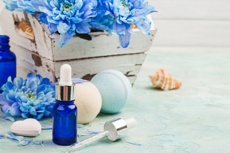 Essential oil spa treatment. Blue flowers and beauty products on concrete background. 스톡 콘텐츠