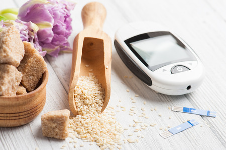 Close up of glucose meter, seeds of sesame and brown sugar on white wooden background. Concept of health control