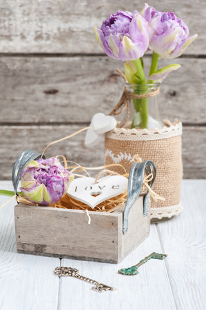 Wooden heart in vintage gift box with key and purple tulips on shabby white background. Copy space for text Stock Photo