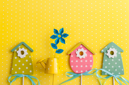 Colorful birdhouses on yellow polka dot background. Easter concept. Stock Photo