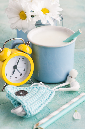 A mug of milk with straw, headphones and blue crocheted holder, yellow alarm clock and flowers on a shabby surface