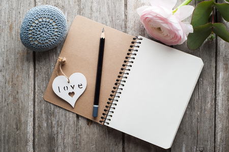 Open notebook, heart, paperweight and flower on shabby wooden table. Concept for journaling, dairy