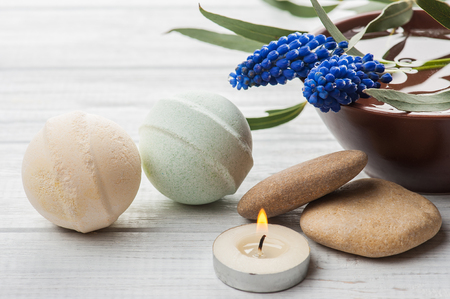 SPA still life, bath bombs and lit cabdle on white wooden background