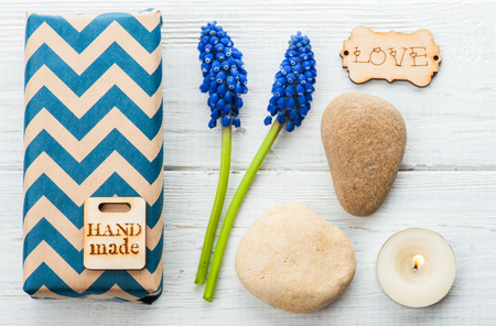 Gift Box with Tag hand made. Wooden background, lit candle, pebbles, blue flowers.