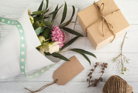 Gift Boxes with Tag. Wooden background, bouqet of flowers.
