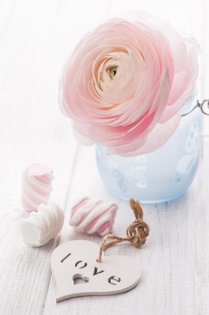 Pink ranunculus, heart and marshmallow on a white wooden background. Pastel colors, greeting card concept with heart Banco de Imagens