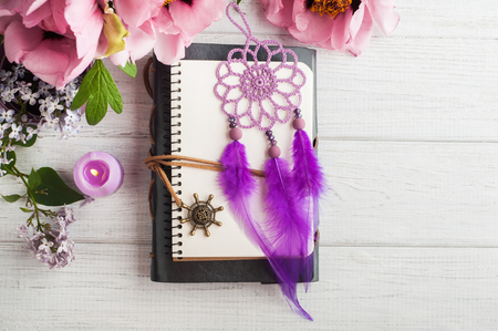 Open notebook, dream catcher, peony and lilac on wooden table. Concept for journaling, dairy
