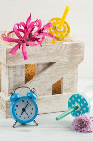 caja de leche: Reloj despertador azul, botellas con lilly rosa y pajitas. Naturaleza muerta en estilo rústico