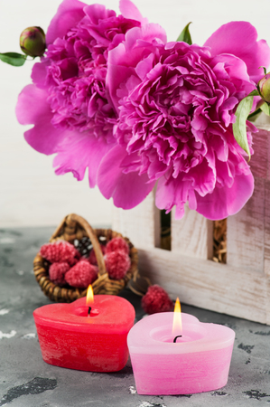bougie coeur: Lit candles heart shaped, purple peonies, raspberry. Valentines or mother day card concept Banque d'images