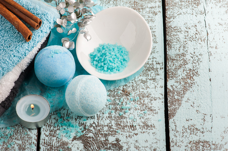 SPA composition with blue bath bombs, candle. Wooden background